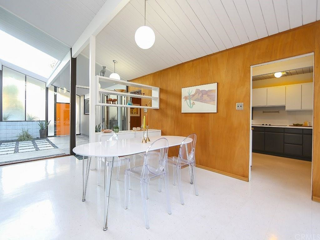 Like many Eichler-designed houses, he implemented Phillippine mahogany walls, which were kept original. The living spaces connect to the atrium from multiple glass-enclosed areas.  Photo 4 of 8 in This Quintessential Eichler Will Hit All Your Midcentury Goals—and It's For Sale