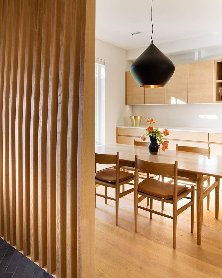The dining area is separated from the entrance with a custom wrap-around screen that provides privacy without closing the space off completely. The slats are made of CNC'ed wood.  Photo 1 of 3 in A Toronto-Based Firm Breathes New Life Into a Victorian's Interior