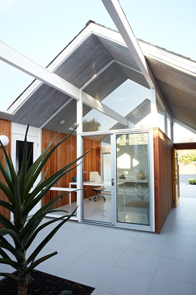 As one of Eichler's courtyard models, the office looks directly through the atrium and into the glass-enclosed living room, providing the ultimate indoor/outdoor feeling. The gray porcelain tile that Klopf Architecture installed in the interior is continued in the atrium.
