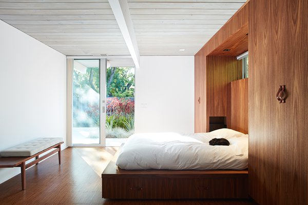 To enlarge the bathroom, they integrated the closet space into the new bathroom, and thus had to create new storage. They designed a custom walnut bed wall in the master bedroom that contains built-in wardrobes.