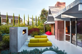 Outer Space Landscape Architects built a custom fireplace in the backyard, which acts as a backstop for the seating area.
