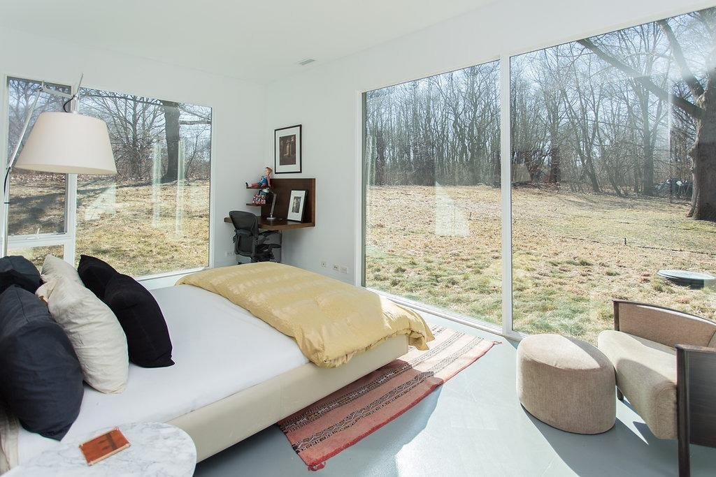 The bedrooms look out to the wooded surroundings through large expanses of glass.  Photo 7 of 9 in Red Cedar Is the Key Ingredient of This Wooded Cottage For Sale