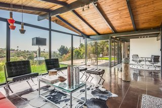 When you enter into the house, you find yourself in an open space that combines the living and dining rooms—and is lined with floor-to-ceiling glass. The dining area is marked by the same aggregate concrete flooring that began in the front of the house.