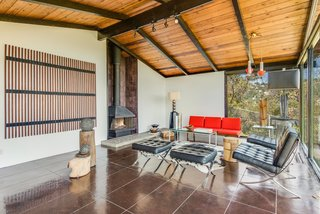 A wall of quarry tile surrounds the freestanding fireplace that takes centerstage in the living room. Cole pointed out that though it's original to the house, its initial orange color has been painted over.