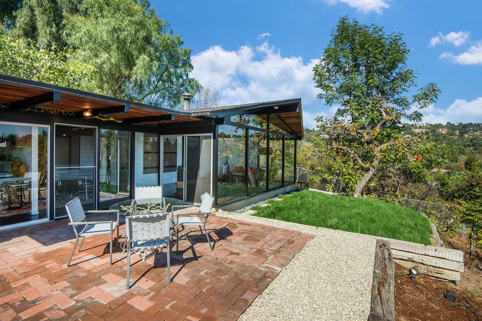 The outdoor living space can be accessed directly from the living area and includes a deck, lawn, and a section that's perfect for an outdoor dining table—which would sit on top of terracotta tile and more aggregate concrete floors.  Photo 10 of 10 in This Midcentury Home For Sale Is Not Your Regular Ranch House