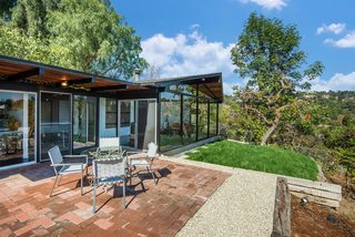 The outdoor space can be accessed directly from the living area and includes a deck, lawn, and a section that's perfect for an outdoor dining table setup—which sits on top of terra cotta tile and more aggregate concrete floors.