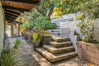 An impressive stone staircase leads down to the entrance of the house. Here, you'll also find an aggregate concrete floor treatment, which continues to be a theme throughout both the interior and exterior.
