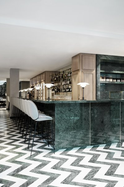 The expansive green marble bar hosts GUBI's Beetle Bar Stools. The entire space is filled with a pleasant green-focused color palette that's offset by shades of gray and brass details.  Photo 6 of 10 in The Revived Maison du Danemark Brings Two New Danish Restaurants to Paris
