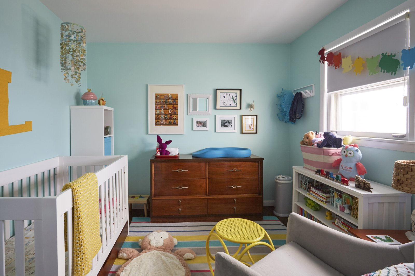 Kids, Neutral, Bedroom, Rug, Rockers, Storage, Bookcase, Toddler, Dresser, and Dark Hardwood Like they thought may be in their future, they now share this home with their two-year-old daughter, whose room shares the upper floor with the master bedroom and the office.  Kids Neutral Rug Dark Hardwood Photos from Clever Storage Solutions and a Shifted Layout Revive This 1950s Chicago Home