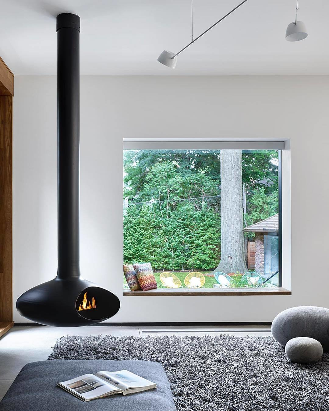 The living space that features a freestanding fireplace looks out through a seated window that perfectly frames the yard.  Photo 3 of 4 in From Front to Back, This Toronto Home Literally Merges Heritage and Modernism