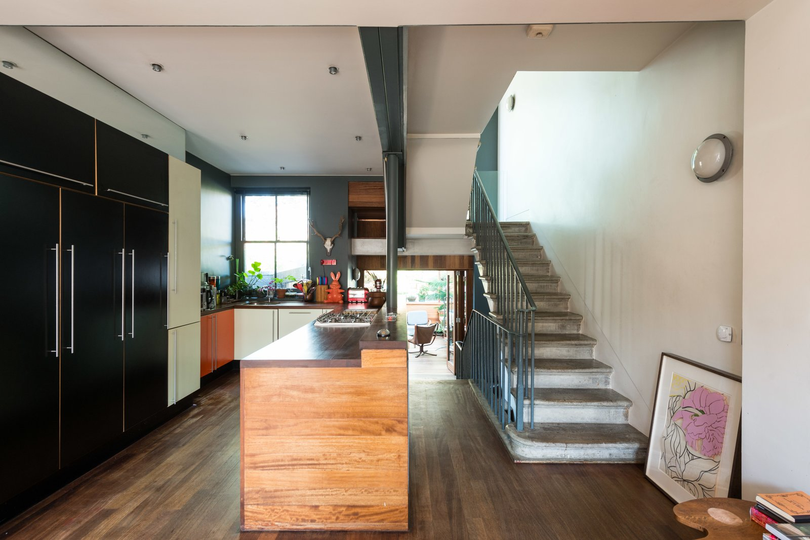 On the other end of the dining space is the kitchen, which contains an extensive island that acts as a divider from the pathway that leads to the garden room. One of the many sets of original concrete stairs is seen on the right.  Photo 5 of 11 in Formerly Home to an Artist and Knitwear Designer, a Commercial Space-Turned-Dwelling Hits the Market