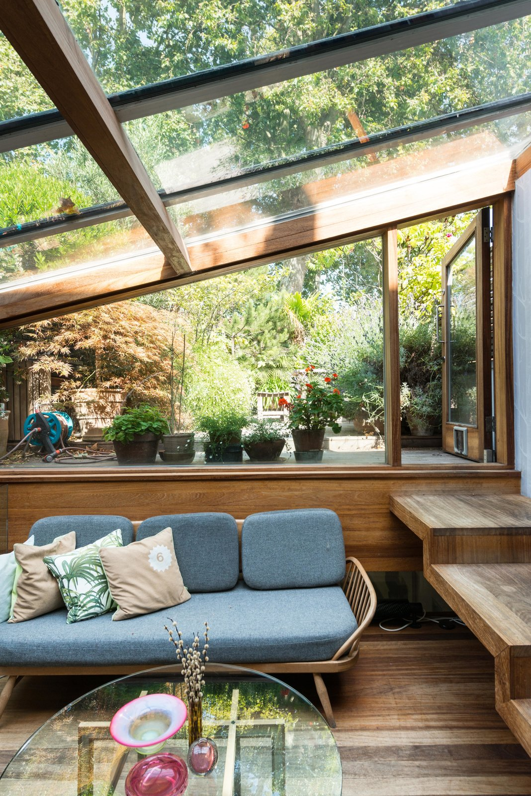 One of the additions that took place during Brinkworth's second phase of extensions, is the glazed garden room, which sits half a level below the first floor. Handcrafted wooden steps lead you to a terraced garden.  Photo 9 of 12 in 10 Examples of Sustainability at Work in Outdoor Spaces from Formerly Home to an Artist and Knitwear Designer, a Commercial Space-Turned-Dwelling Hits the Market