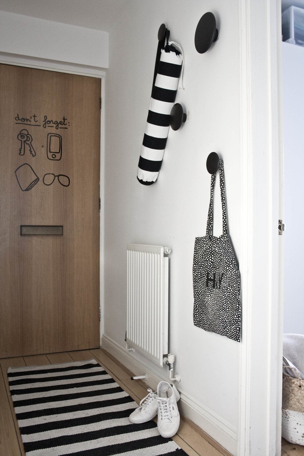 Doors, Interior, and Wood While trying to introduce some charm and playfulness into the space, Silvia discovered a set of reminder stickers from Hu2 that she stuck to the inside of the front door. She also mounted four of Muuto's Dots, which were designed by Lars Tornøe and are both useful and decorative.  Photo 2 of 8 in Two Architects Revive Their London Flat With Minimal Furnishings and a Fresh Dose of White
