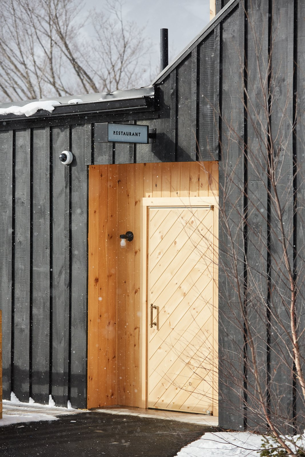 Doors, Swing Door Type, Wood, and Exterior The exterior of the structure is wrapped with board-and-batten boards that have been milled locally and finished with a dark stain. It's balanced out by sections and accents made with natural pine and cedar.  Photo 8 of 14 in A Modern Mountain Lodge That Will Make You Love Winter Like Never Before