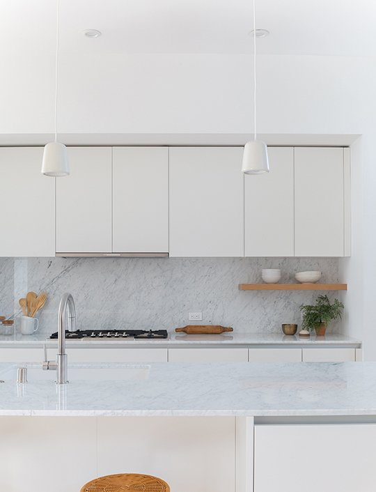 The kitchen, which boasts and 11-foot island with seating for three, have Carrera marble countertops and backlashes and stainless-steel appliances from Bosch and Miele.  Photo 4 of 4 in A Small Development in Los Feliz Offers Scandinavian-Inspired Urban Living