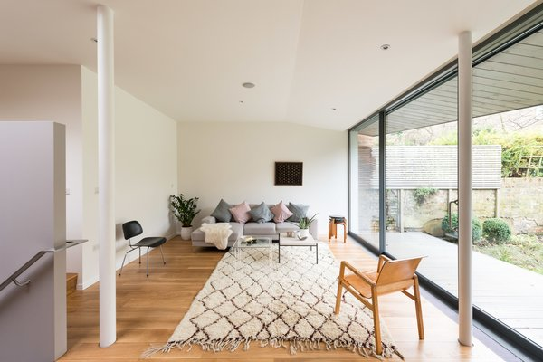 By following a set of steps, you enter into a sitting room that's part of the extension that was built towards the rear of the house. A large sliding wall of glazed glass from Fineline opens to the outside.  Photo 5 of 9 in A Fusion of Old and New Makes this Home For Sale Shine on London's Womersley Road