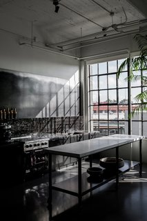 Directly next to the dining area is the dark kitchen, which has a custom island made with a metal base and a CoorItalia Calacatta marble top. Designed by Chris French, it's meant to invite socializing.