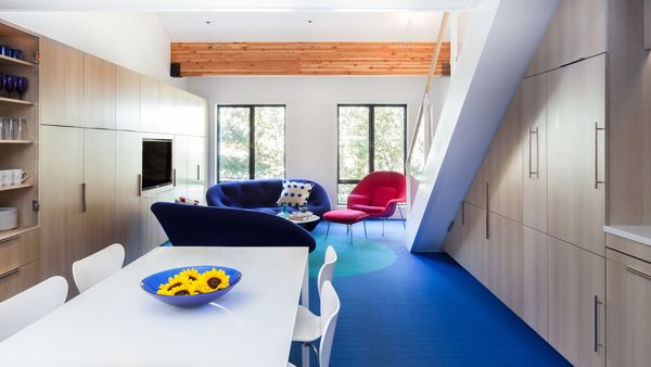 Simon preserved the structural beams from the building, but put a fresh sprin on the rest of the surfaces. The Plume sofas by Ligne Roset are upholstered in a bright cobalt blue quilted blend fabric, while the Womb Chair—designed by Eero Saarinen for Knoll—is finished in a bold magenta fabric.  Photo 2 of 10 in Bright Colors and Sleek White Oak Fill This Playful Lake Tahoe Loft