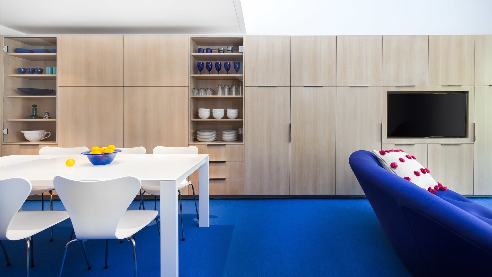 Because of the loft's specific layout, they knew they had to maximize the space by creating a massive amount of storage. Shown here is one of the walls that's lined with flush-mounted cabinets by David Amble Cabinetry. The dining table is surrounded by Arne Jacobsen Series 7 Chairs.  Photo 10 of 10 in Bright Colors and Sleek White Oak Fill This Playful Lake Tahoe Loft