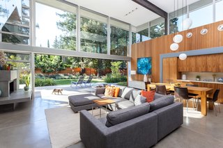The double-height great room encompasses much of the completely renewed section in the middle of the home—which includes the living, dining, and kitchen spaces. Since the existing floor slabs had cracks in them, Jay and Melissa floated new concrete floor slabs over the existing. They replicated the original as close as possible, and polished the final result.