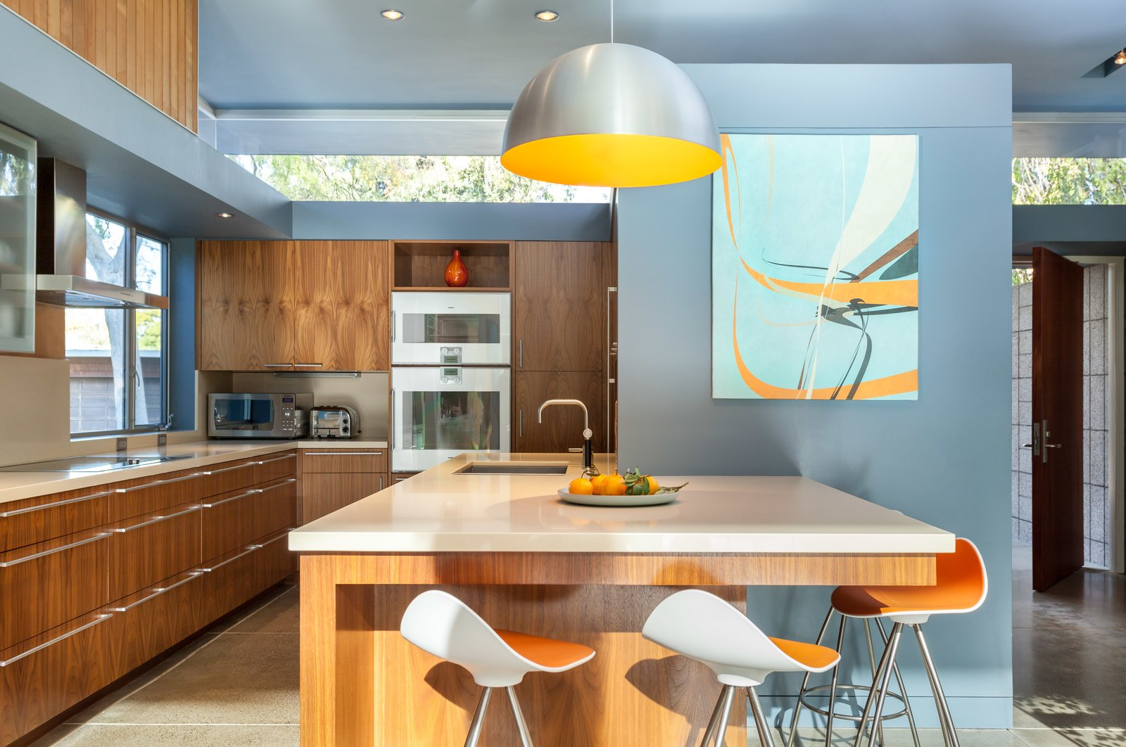 The kitchen is part of the new section in the center and features clerestory windows that let natural light floor into the space.  Photo 8 of 11 in A Year of Careful Study Leads to a Thoughtful Renovation of a 1949 Eichler