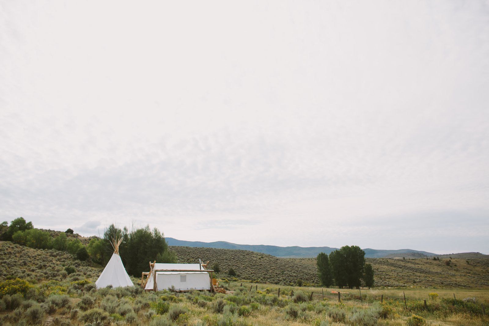 The team behind Collective Retreats built the custom canvas tents with wood that they sourced locally. They used timber they found in the property's vicinity to hold the peaks together at the top. Shown here is the Yellowstone location. Tagged: Outdoor, Field, Trees, Grass, and Shrubs.  Photo 2 of 12 in Get the Modern Camping Experience You Crave at One of These New Secluded Retreats