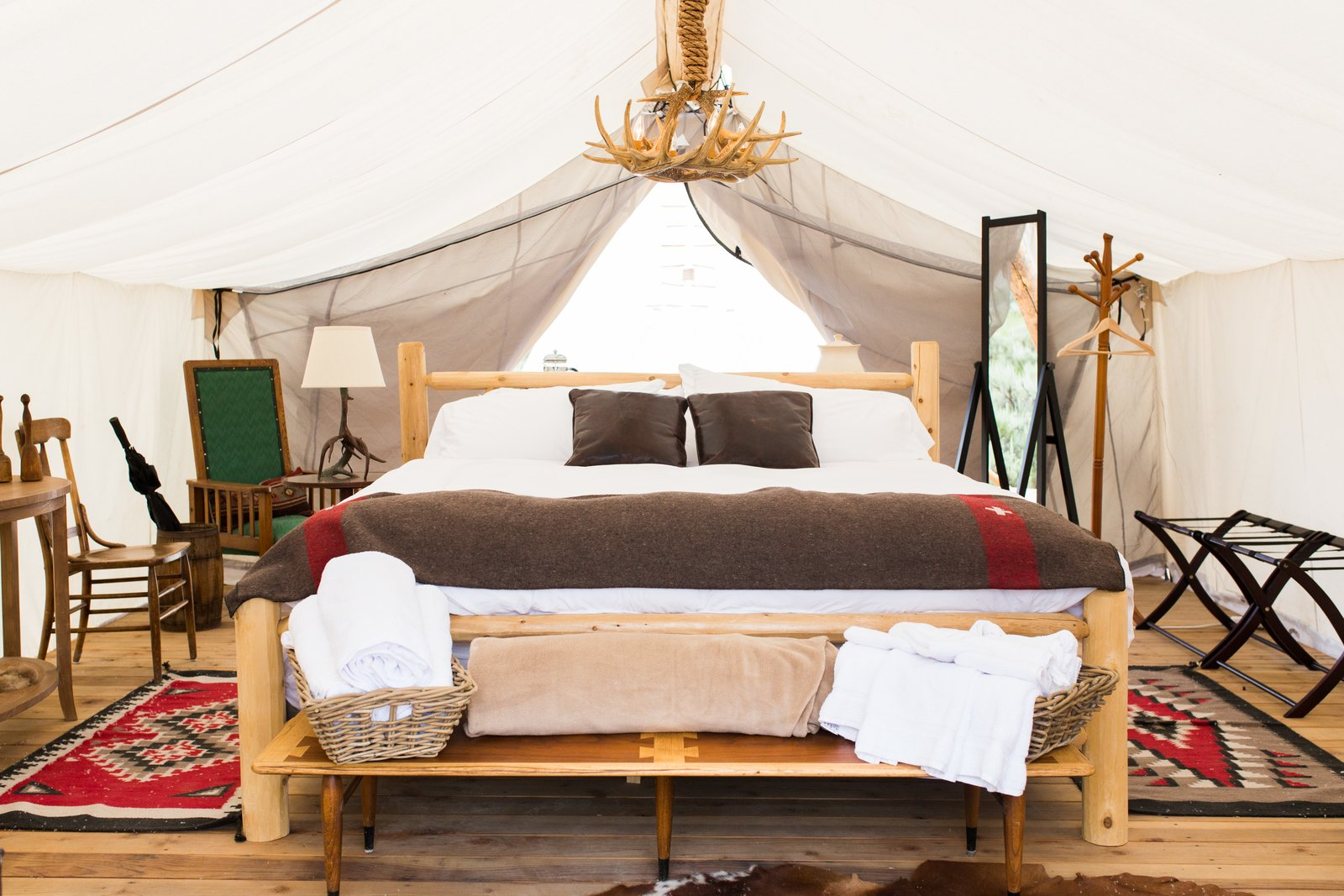 Tented bedroom with table lamp and center hanging pendant light with antler facades