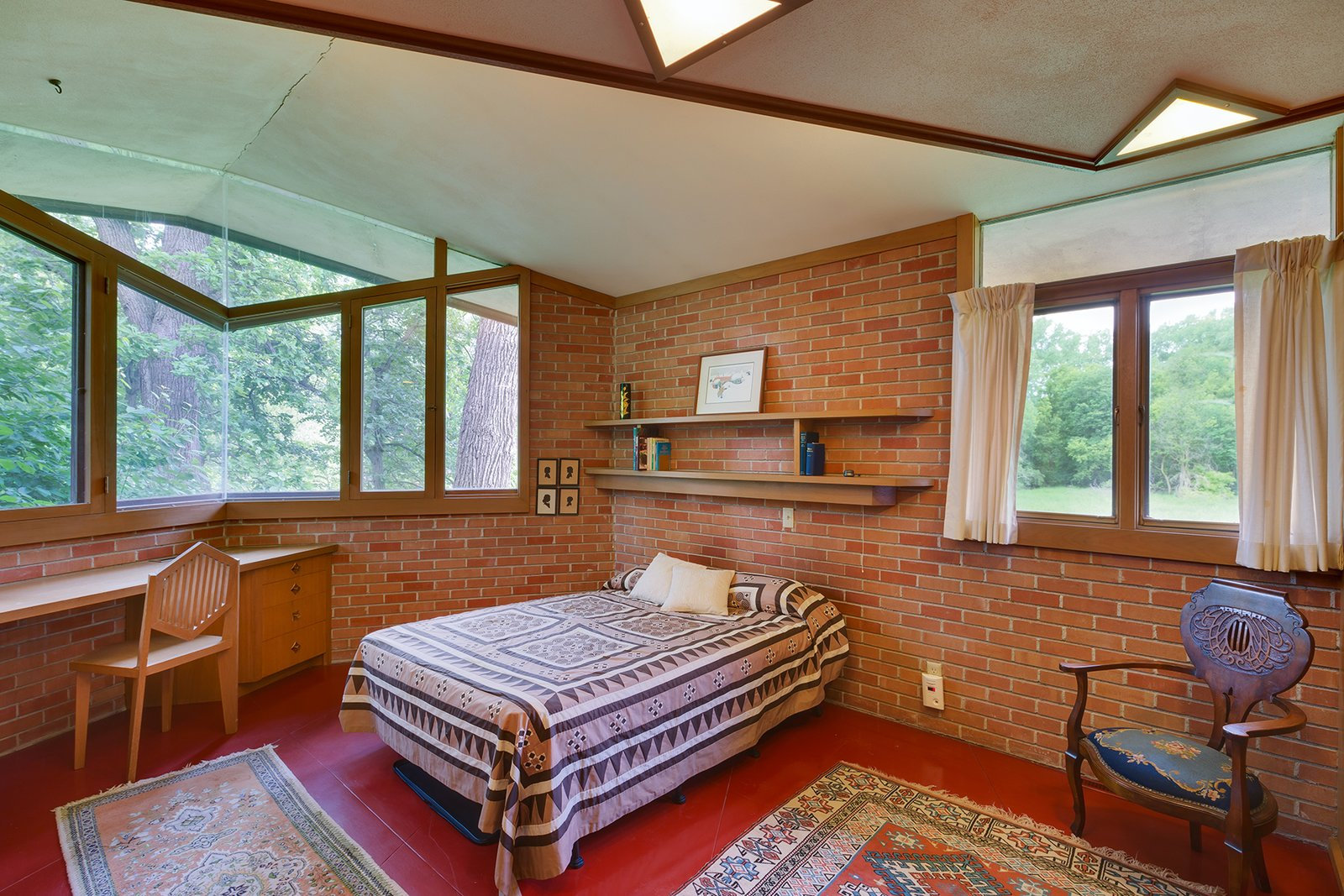 In one of the three bedrooms, Wright designed a built-in desk and graphic chair. The angular windows and skylights are continued into the bedrooms.  Photo 7 of 8 in The Original Homeowners of a Frank Lloyd Wright-Designed House Ask $1.3 Million