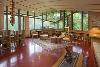 The open living space is surrounded by large, angular pieces of glass and sits on a Colorundum floor painted in Cherokee Red—a material and color that Wright often used in his work. This space also includes a brick wood-burning fireplace.
