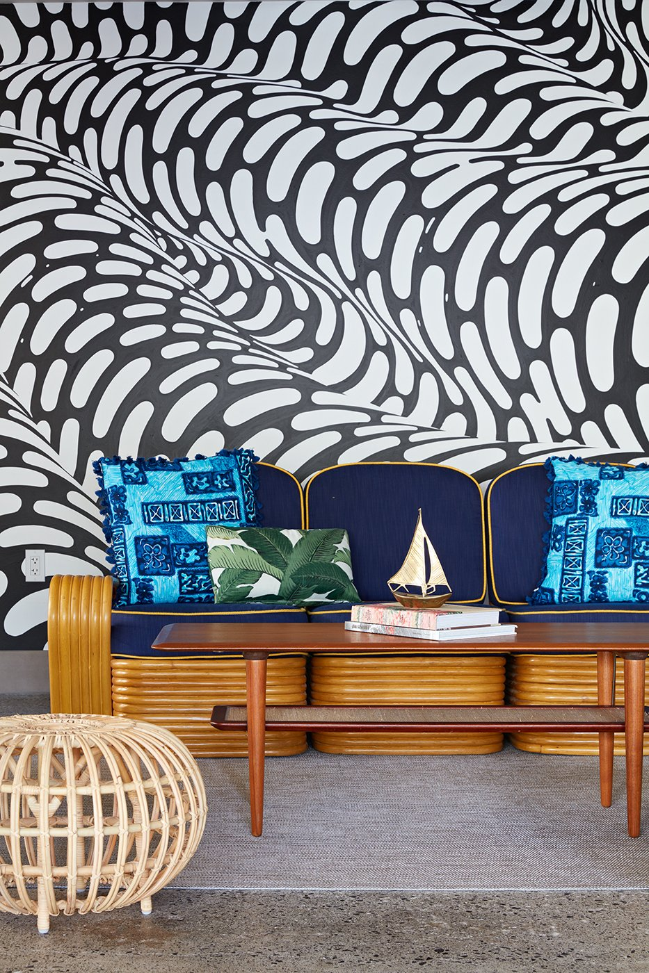"""Living Room, Sofa, Ottomans, and Coffee Tables In the covered cabana area by the pool, a hand-painted mural by Brendan """"The Blob"""" Monroe creates a funky backdrop that's inspired by the flow of water. Local artist, illustrator, and curator Jasper Wong co-curated the mural artwork found throughout the property.  The Surfjack Hotel & Swim Club from This Surf-Inspired Hotel Celebrates Waikiki's Creative Spirit and its Midcentury Roots"""