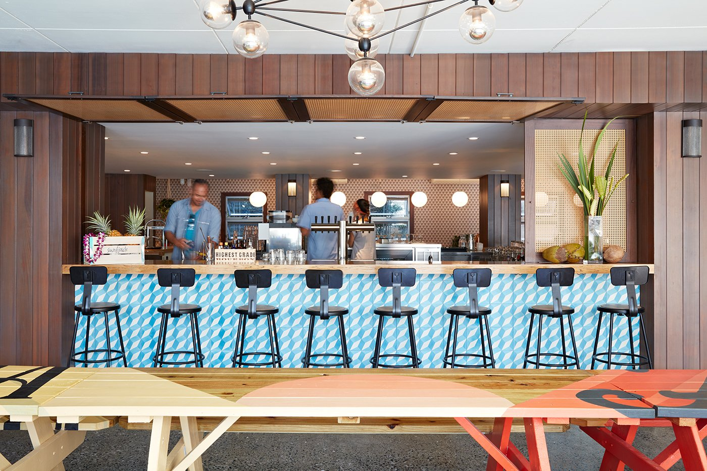 "Dining Room, Bar, Stools, Pendant Lighting, and Table As chef Ed Kenney's fourth eatery, Mahina & Sun's believes in, ""local first; organic whenever possible; with aloha always."" The picnic tables next to the bar were hand-painted by local artist Jeff Gress.  The Surfjack Hotel & Swim Club from This Surf-Inspired Hotel Celebrates Waikiki's Creative Spirit and its Midcentury Roots"