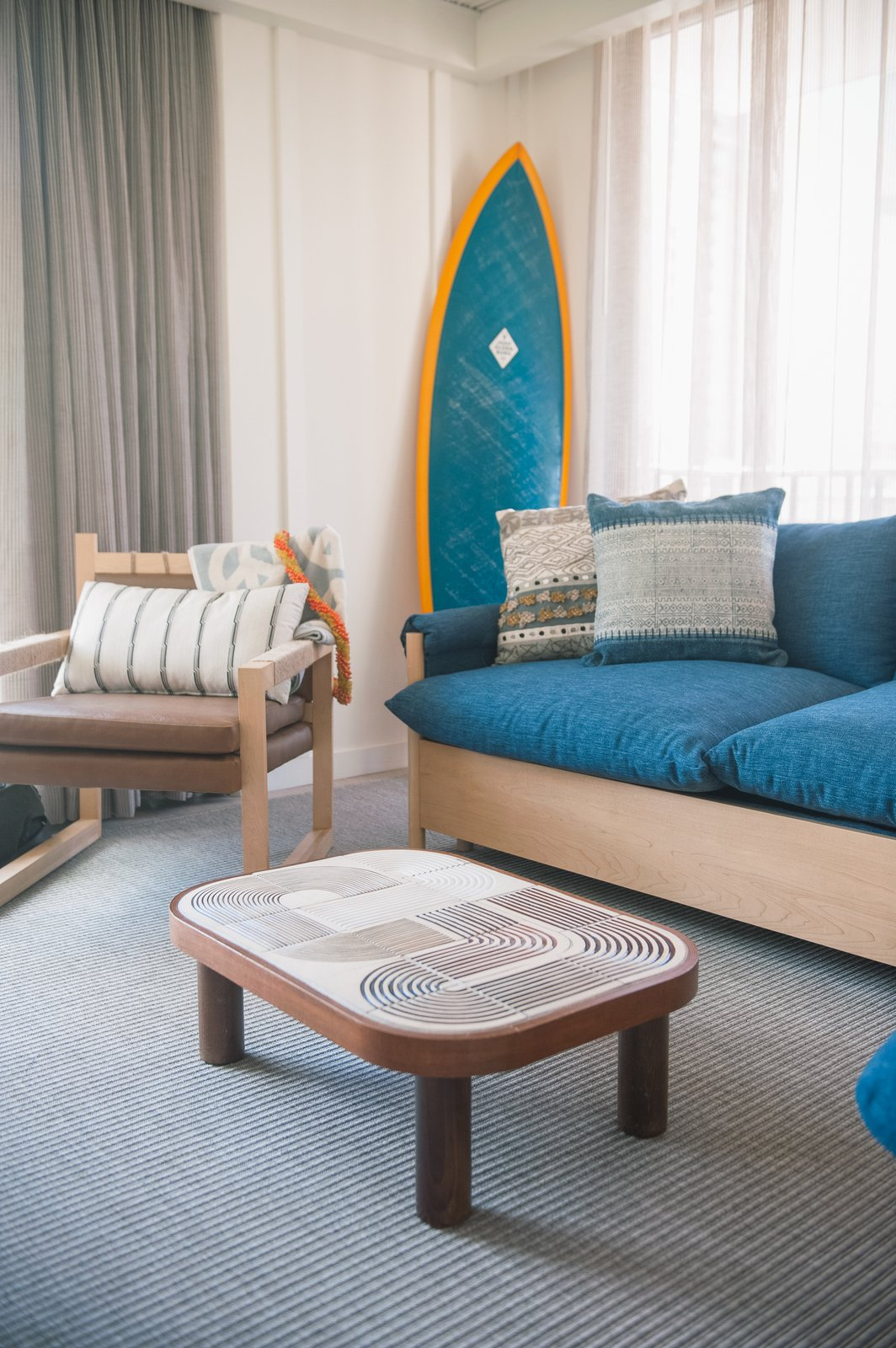 Living Room, Sofa, Chair, Coffee Tables, and Carpet Floor Studio Collective designed the 112 rooms based on the bungalows of Oahu's North Shore. They feature reed ceilings, batten walls, local art, and bespoke coffee tables that are topped with ceramic tiles.  Photo 11 of 14 in This Surf-Inspired Hotel Celebrates Waikiki's Creative Spirit and its Midcentury Roots