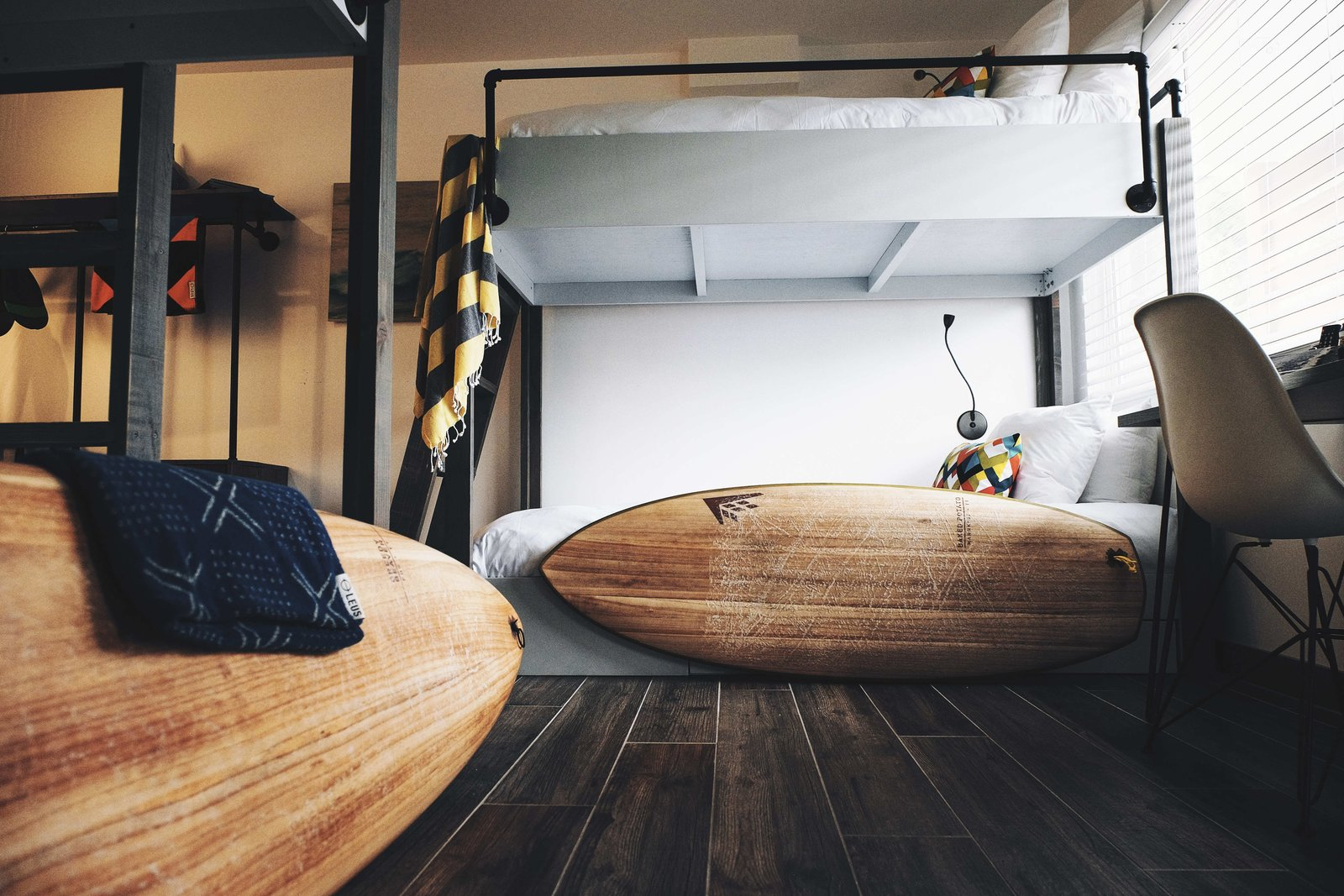 """Bedroom, Bunks, and Dark Hardwood Floor All of the rooms can accommodate two guests, except for """"Pipes,"""" which includes a set of camp-style bunk beds that can fit four people. Guests have access to the hotel's surf equipment, including a quiver that's filled with Firewire surfboards. They also have partnerships set up with a handful of other local business so that they can offer guests whatever it takes to complete the experience.  Photo 9 of 11 in A New Modern Hotel in San Diego Offers Surfing Adventures and Local Hospitality"""