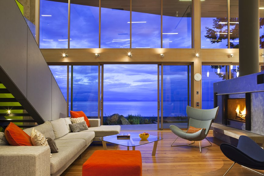 The broad interior two-story living room is a thickened wooden frame to view the Georgia Straight beyond, where wild winter storms rage and bald eagles hunt.   #livingroom #bright #hearth #beachhouse #beachhouses #evening #oceanfront #oceanviews #britishcolumbia #vancouverislands #comox #interstice #intersticearchitects #interiordesign #bradlaughton #bradlaughtonphotography  TreeHugger