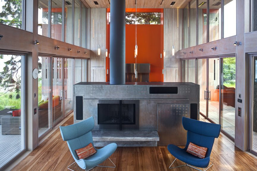 Corrugated-steel room divider / hearth with a fireplace inside.   #interstice #intersticearchitects #hearth #roomdivider  #bradlaughton #bradlaughtonphotography #orange #bright #color #kitchen #livingroom #diningroom #cabinetry  #highceilings #beachhouses #beachhouse  #britishcolumbia #vancouverisland #smokestack  TreeHugger