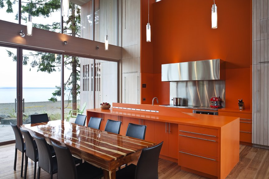 Woven through the raw palette of glass, concrete, wood, and Corten steel are two strong color gestures, including this bright orange paint and corian countertops and cabinetry.    #kitchen #corian #custom #waterfront #oceanfront #view #diningroom #orange #bright #color #beachhouse #beachhouses #vancouverisland #britishcolumbia #view #interstice #intersticearchitects #bradlaughtonphotography #bradlaughton  TreeHugger