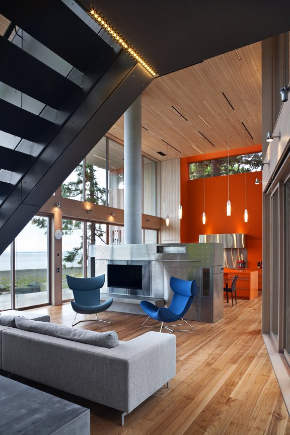 A bold orange vertical excavation of the frame accents the kitchen and provides a second bright counterpoint to the long, grey, Canadian winters.   #kitchen #bright #color #orange #hearth #livingroom #beachhouse #oceanfront #beachhouses #britishcolumbia #vancouverisland #interstice #intersticearchitects #bradlaughton #bradlaughtonphotography   TreeHugger