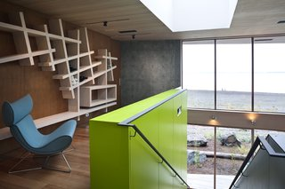 An intimate, peaceful study area at the top of the staircase provides a quiet moment for guests, and unique storage solutions in the cabinetry and shelving.   #shelving #green #limegreen #bright #color #staircase #storage #beachhouse #beachouses #interstice #intersticearchitects #bradlaughton #bradlaughtonphotography #britishcolumbia #vancouverisland