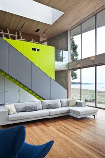 A sleek  staircase leads from the living room to a study. The bright green accent wall includes storage for a projector and book case.   #green #limegreen #bright #color #livingroom #entertainmentroom #staircase #storage #beachhouse #beachouses #interstice #intersticearchitects #bradlaughton #bradlaughtonphotography #britishcolumbia #vancouverisland