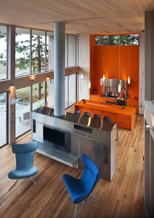 The kitchen and dining area is an open space which is filled with bright, warm  color, in this case an island and cabinets in orange Corian.  #orange #bright #color #kitchen #livingroom #diningroom #cabinetry #corian #hearth #highceilings #beachhouses #beachhouse #interstice #intersticearchitects #bradlaughton #bradlaughtonphotography #britishcolumbia #vancouverisland   TreeHugger