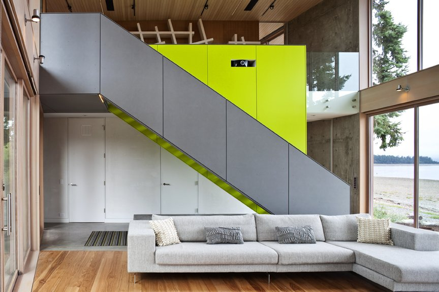 A sleek  staircase leads from the living room to a study. The bright green accent wall includes storage for a projector and book case.   #green #limegreen #bright #color #livingroom #entertainmentroom #staircase #storage #beachhouse #beachouses #interstice #intersticearchitects #bradlaughton #bradlaughtonphotography #britishcolumbia #vancouverisland  TreeHugger