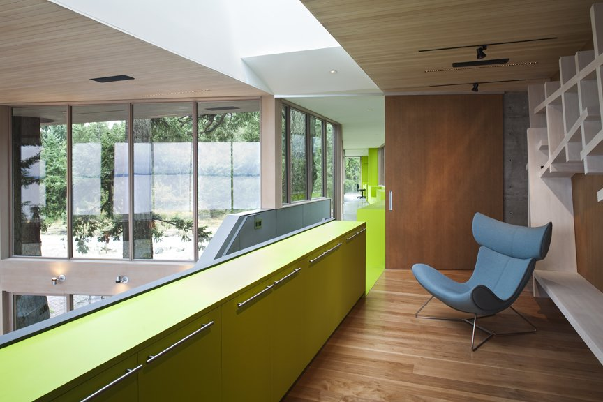 This strong color gesture of green traces the entry path from the guest house to the main house, providing cabinetry along the glass walk way. The door to the walkway, which is opened in this photo, slides closed to divide off the two volumes.   #green #limegreen #bright #color #walkway #hallway #staircase #storage #beachhouse #beachouses #interstice #intersticearchitects #bradlaughton #bradlaughtonphotography #britishcolumbia #vancouverisland  TreeHugger