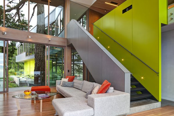 A sleek  staircase leads from the living room to a study. The bright green accent wall includes storage.   #green #limegreen #bright #color #livingroom #entertainmentroom #staircase #storage #beachhouse #beachouses #interstice #intersticearchitects #bradlaughton #bradlaughtonphotography #britishcolumbia #vancouverisland