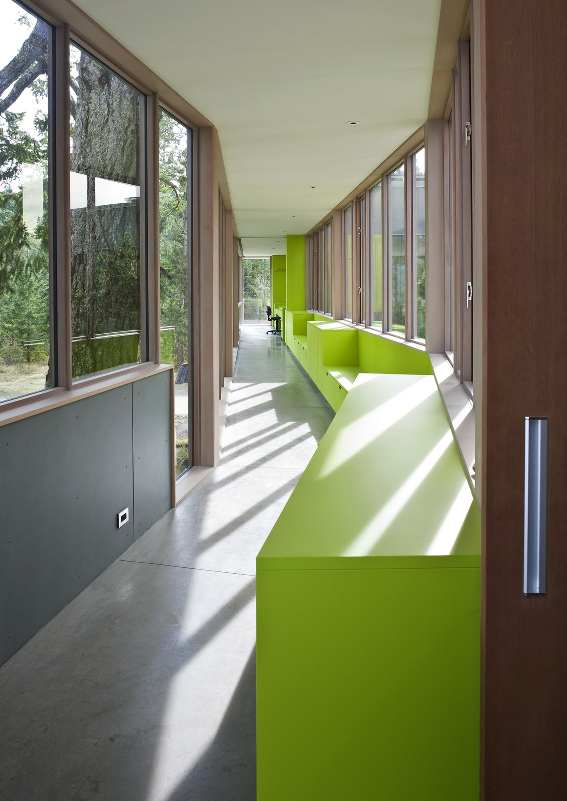 The semi-enclosed glass bridge walkway extends through the trees from the seasonally closable Guest house . The bright green color follows into the walkway, and covers the custom cabinetry and seating along the bridge.   #bridge #walkway #green #limegreen #glass #residential #hallway #beachhouse #beachhouses #bright #color #interstice #intersticearchitects #britishcolumbia #vancouverisland #bradlaughton #bradlaughtonphotography   TreeHugger