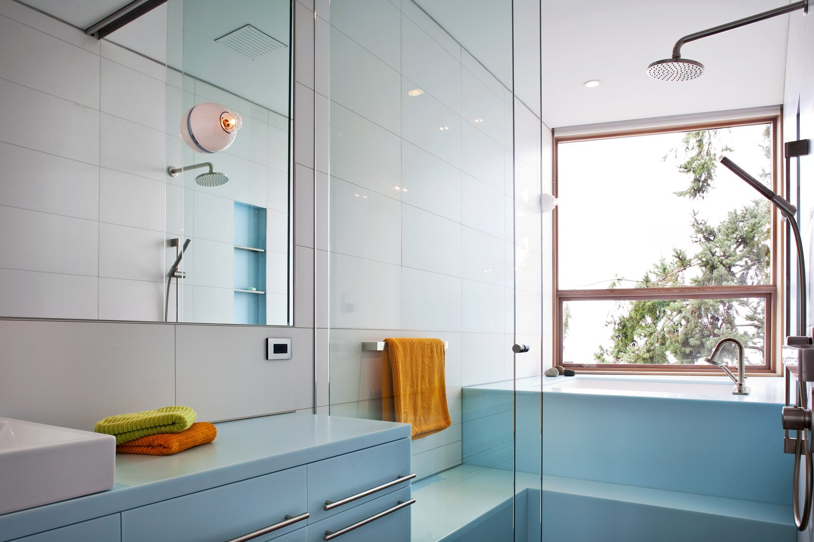 The pale blue of this bathroom in the main house creates a peaceful, serene atmosphere. The seating shower stalls, and a tub that provides a view to the outdoors makes for an incredibly luxurious, rejuvenating experience.   #paleblue #bathroom #shower #bath #tub #color #bright #beachhouse #glass #showerdoor #minimal #modern #relaxing #spa #interstice #intersticearchitects #interiorarchitecture #bathroomdesign #bradlaughton #bradlaughtonphotography   TreeHugger