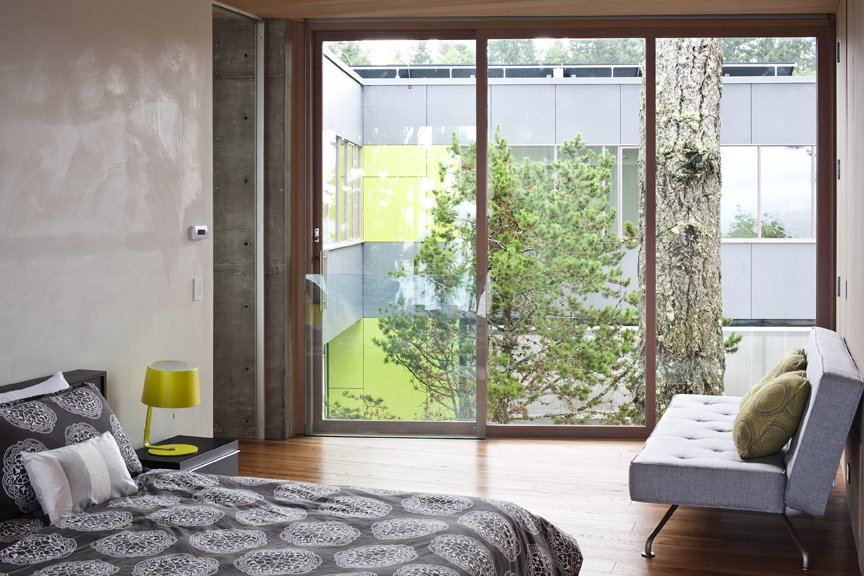 The minimal bedroom reflects the raw material palette of glass, concrete, wood, and Corten steel. This bedroom has a view to the separate volume, and to a large Douglas fir between the two  spaces.   #bedroom #nature #residential #interstice #intersticearchitects #bradlaughton #bradlaughtonphotography  TreeHugger