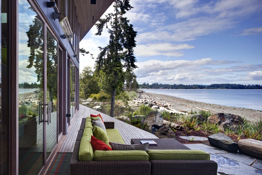 The main house is clad in the local Douglas fir with deep protective eaves, stained grey to match the sun-bleached drift wood logs that litter the coast. #facade #residential #residentialarchitecture #coastline #beachhouse #beachhouses #view #porch #beachfront #britishcolumbia #vancouverislands #bradlaughton #bradlaughtonphotography  TreeHugger