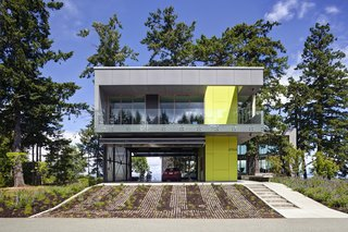 """From the street a vegetated drive bridges the site to the vehicular """"pad"""". From here a semi-enclosed bridge extends through the trees to the wood clad main house beyond. The seasonably closable upper guest house protects the cars in an unconditioned porte-cochere concealed by enormous folding translucent panel doors.   #garage #portecochere #beachhouse #driveway #vegetation #guesthouse #beachhouses #britishcolumbia #limegreen #color #bright #glass #steel #mineralfinish #landscape #green #interstice #intersticearchitects #residential #residentialarchitecture #danlaughton #danlaughtonphotography"""