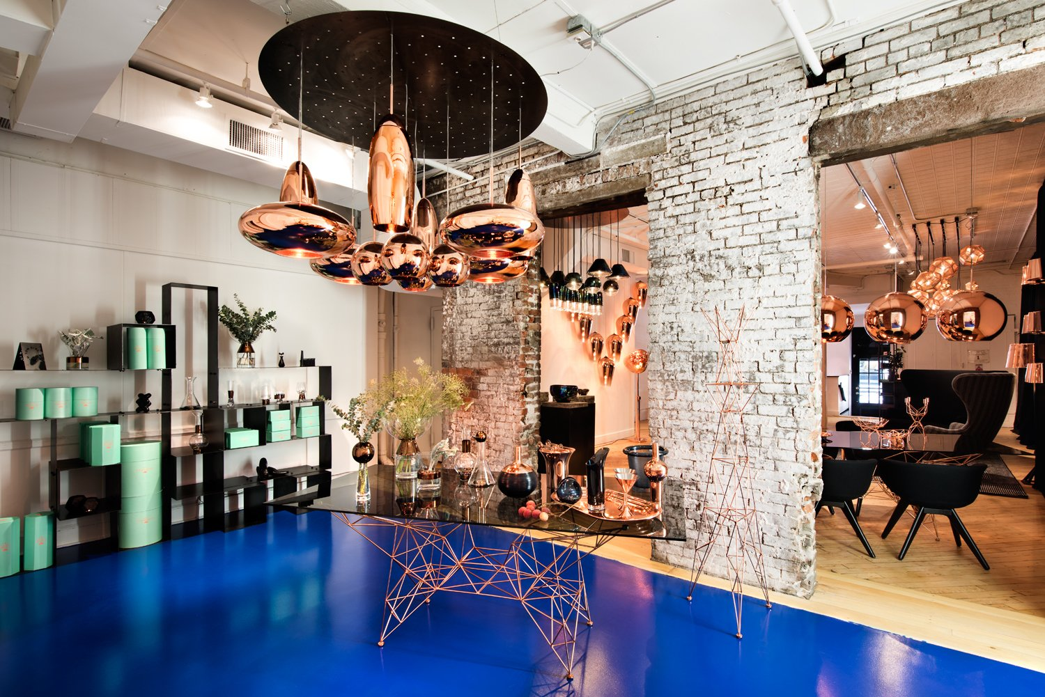 Tom Dixon's new Manhattan showroom at 19 Howard Street, featuring various pendants and tabletop items from the designer's Copper series, and the Pylons dining table, made from a copper-plated steel rod base and smoked glass surface.  Photo 2 of 3 in Twenty Minutes With:  Tom Dixon