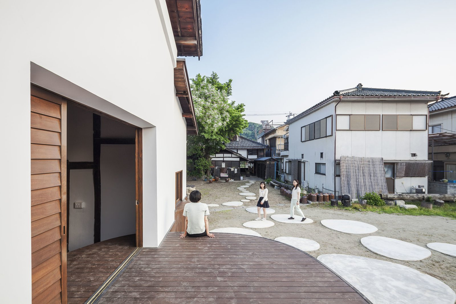 Outdoor, Side Yard, Walkways, Wood Patio, Porch, Deck, and Decking Patio, Porch, Deck Extending to the outdoors, the stage invites engagement from passersby.  Photo 6 of 8 in Saved From Demolition, a Japanese Sake Warehouse Sees a Second Life